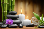zen picture of green bamboo stalks, black stones, purple orchid, white candles and a white folded towel - spa like