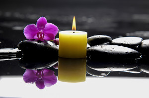 purple orchid and yellow candle on black stones and water for meditation classes