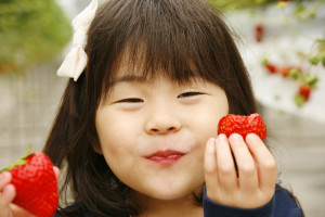 Asian girl holding strawberry and smiling