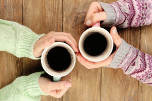 Female hands holding cups of coffee on rustic wooden table