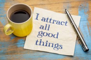 I attract all good things - positive affirmation words - handwriting on a napkin with a yellow cup of coffee