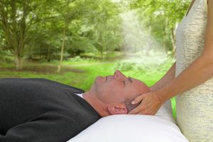 man lying on massage table outdoors getting a Reiki treatment with the white light of Reiki showing in the photo